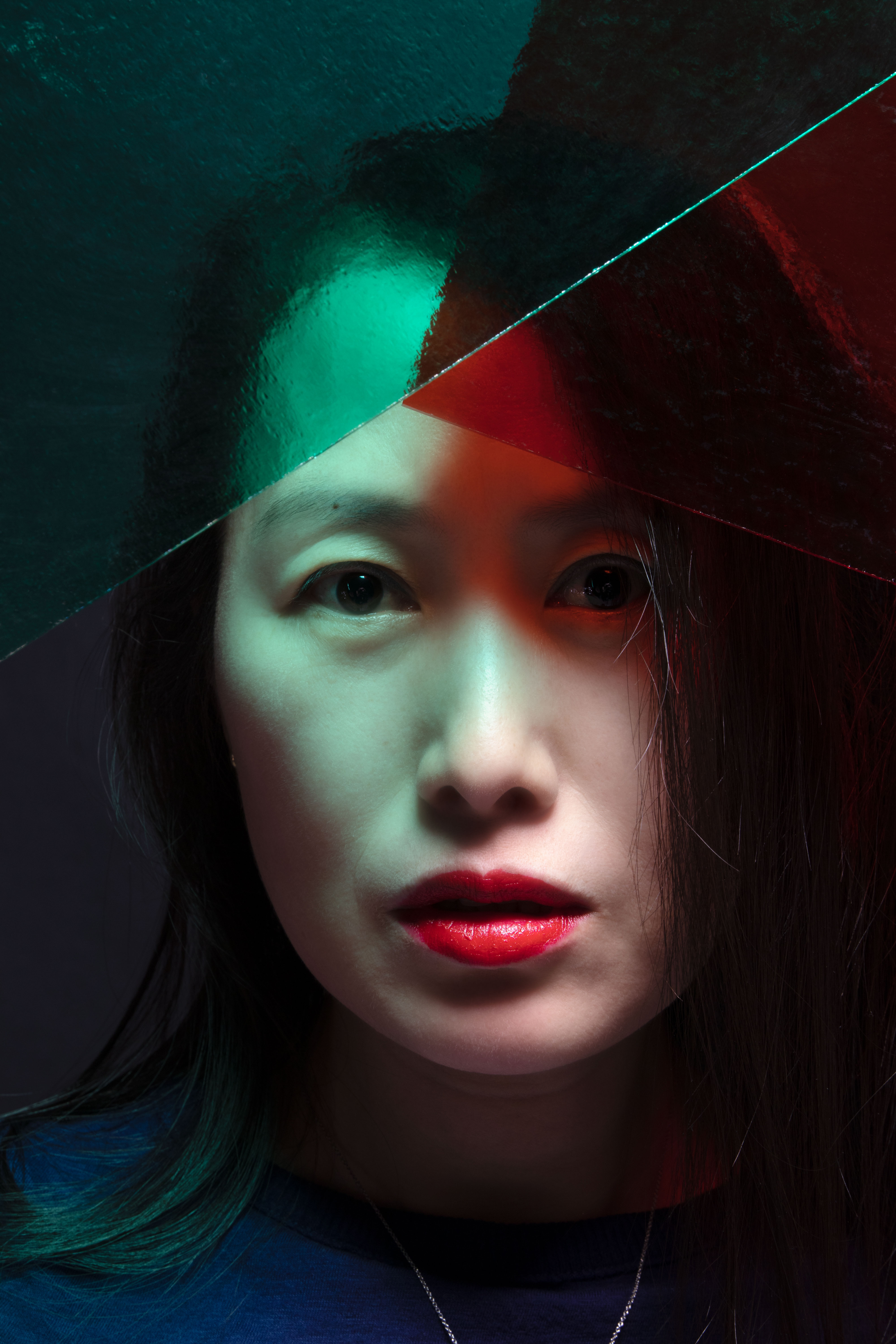 A Korean-American woman with shoulder length straight black hair wearing only red lipstick with a navy shirt and silver necklace stares straight into the camera past planes of pale green and rich red glass angled to a point above her eyes.