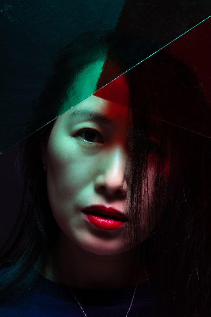 A Korean-American woman with shoulder length straight black hair wearing only red lipstick with a navy shirt and silver necklace stares straight into the camera past planes of pale green and rich red glass angled to a point above her eyes. He head tilts slightly to the right of the viewer, and her hair falls over her left eye.