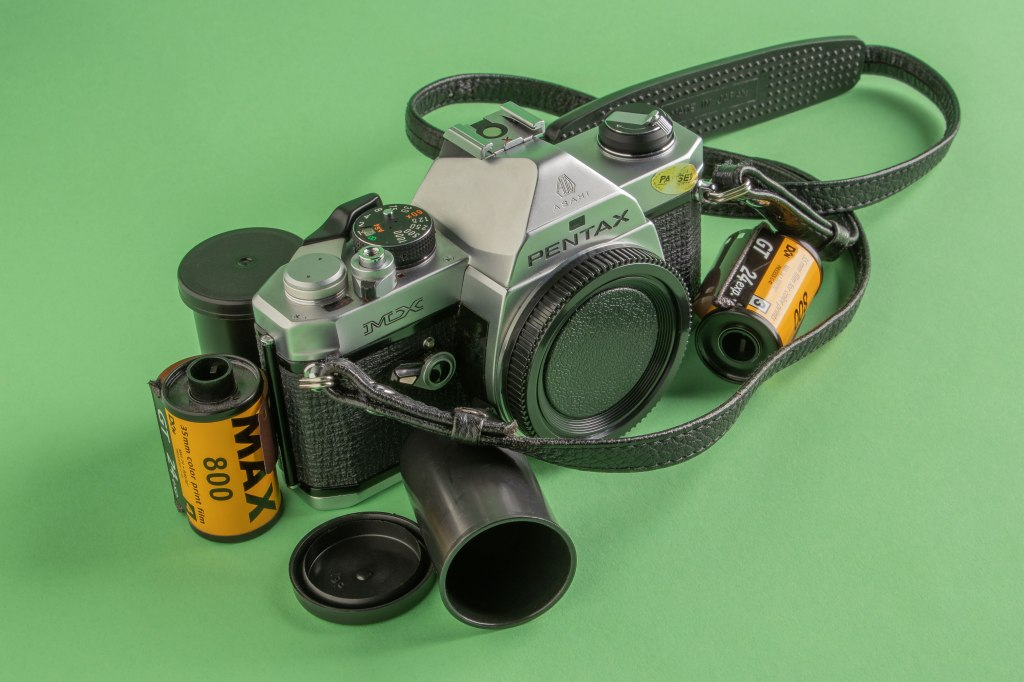 A 1976 Pentax MX silver and black film camera centered between two rolls of Kodak film and two film canisters on a pale green background.