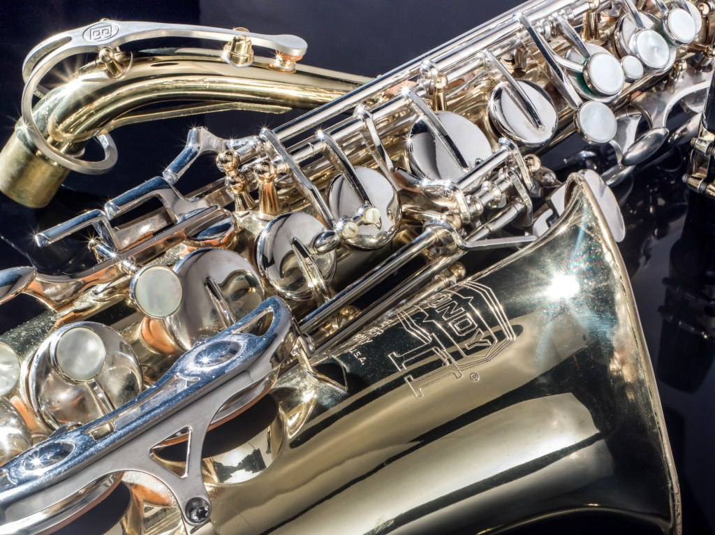 A close up of a gold E-flat alto saxophone with silver and mother of pearl keys lying on black plexiglass, cropped to show the curve of the bell, reflection of the black mouthpiece placed just to the right of the instrument, and the curve of the unattached neck of the saxophone nestled above the body to the image's upper left corner.