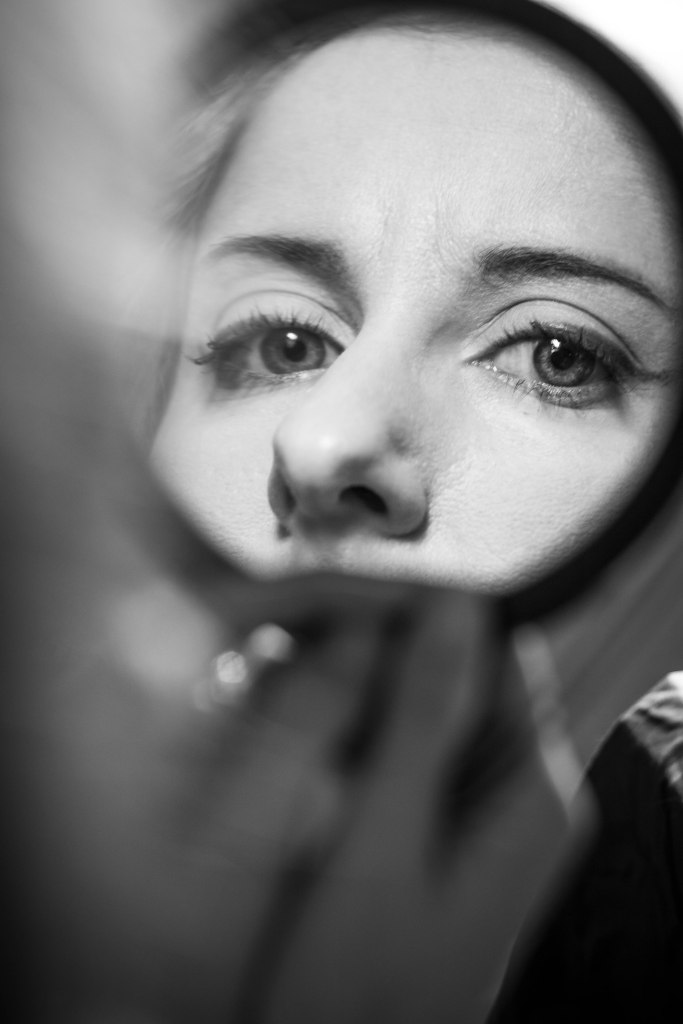 A greyscale image of a woman looking back at the viewer over her shoulder through the hand mirror she holds, framing her eyes and nose only.