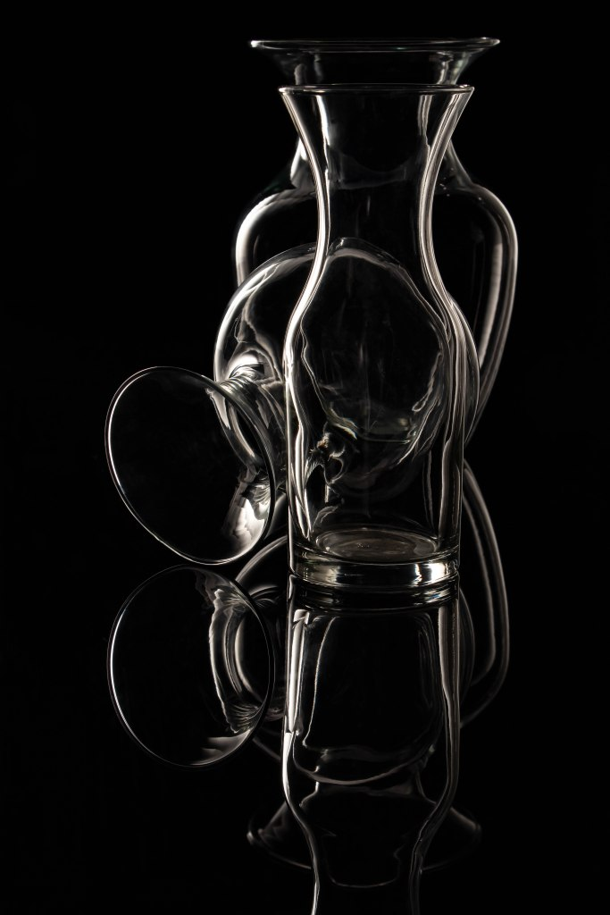 An empty glass wine decanter centered in front of two empty glass vases, one on its side just behind it, the mouth open towards the viewer on the left, and a taller urn-shaped vase behind them both. Only the white edges of the glass highlights are visible against a solid black background with a reflection of the glassware below on the black plexiglass.