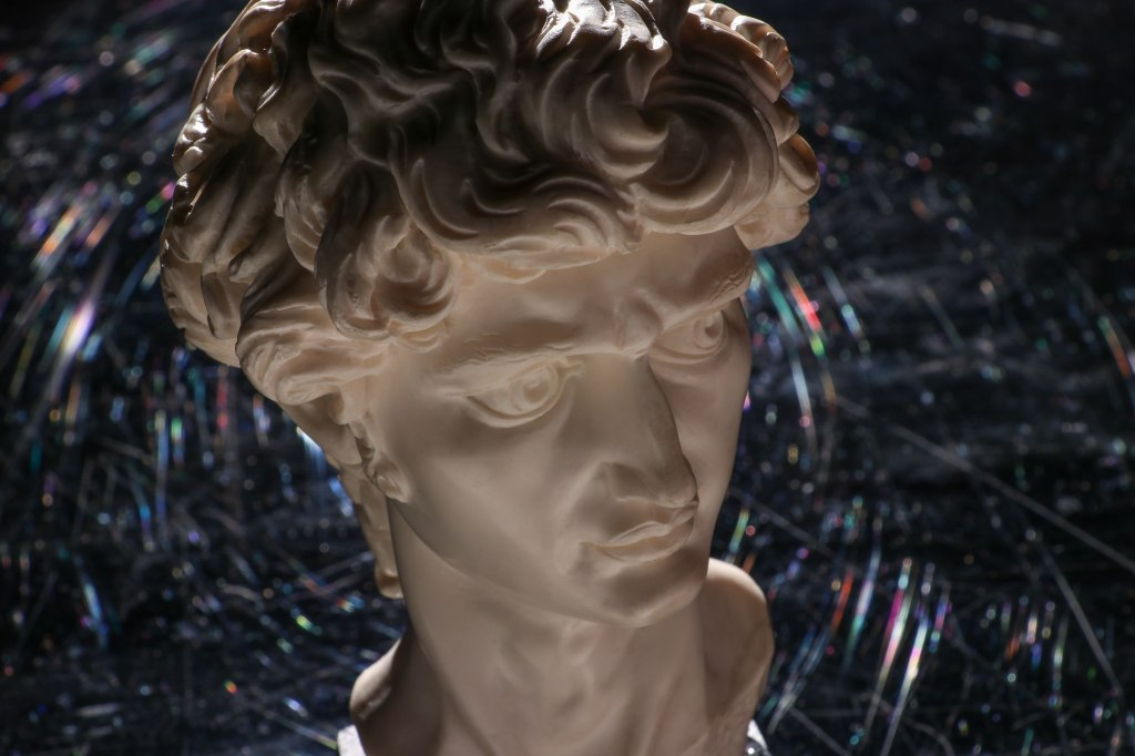 A replication of the marble bust or head of Michelangelo's David sculpture on a black plexiglass background with a prismatic halo in the natural scratches of the surface.