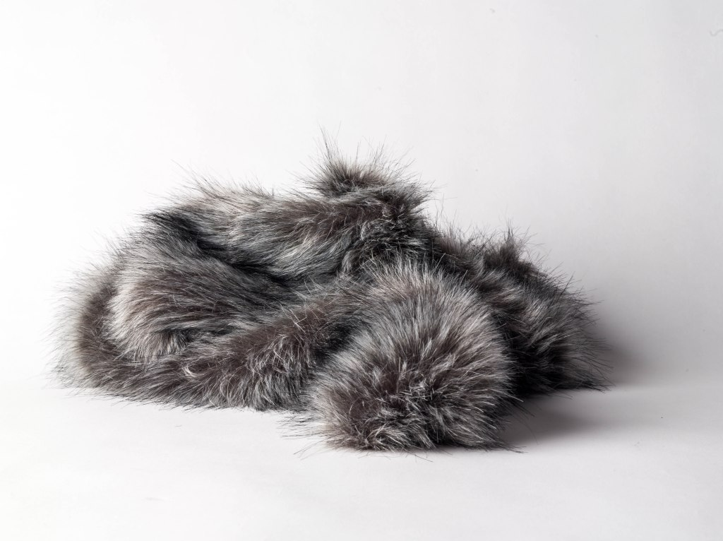 A silver grey faux fox fur stole curled to look like a sleeping cat on a white background.