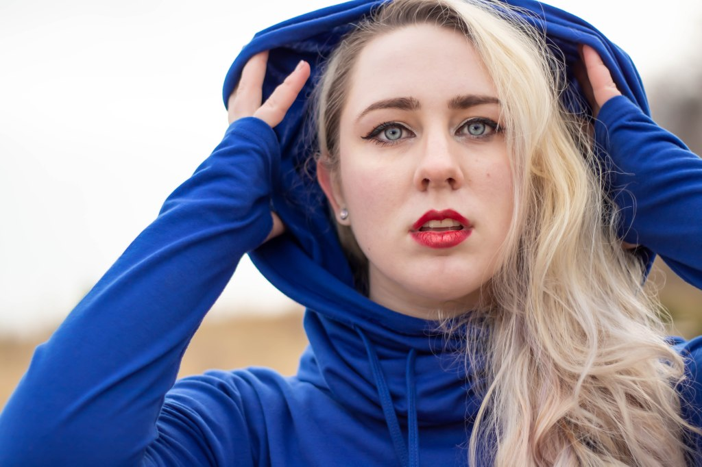 A blonde non binary woman with curly hair, blue eyes, and red lips throws back a rich navy blue hood with both hands.