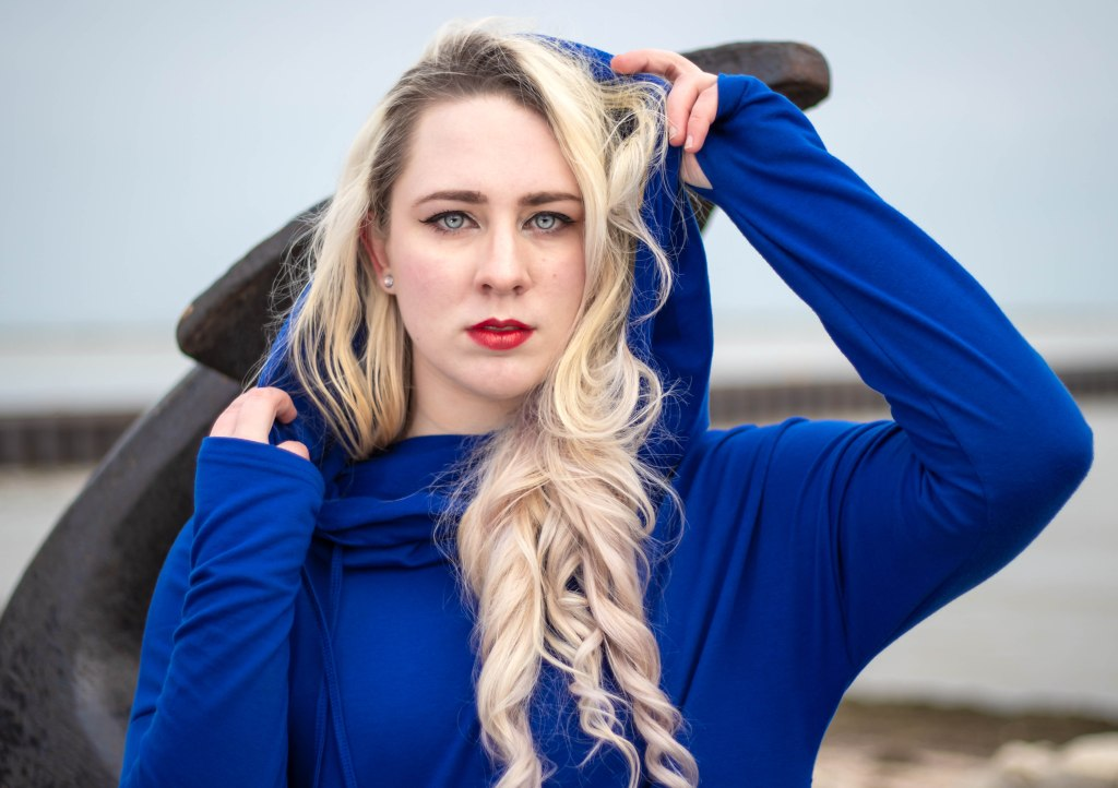 A nonbinary woman with long blonde curls and striking blue eyes and red lips wearing a rich blue hooded sweatshirt standing before a statue of an anchor in Kewaunee, WI.