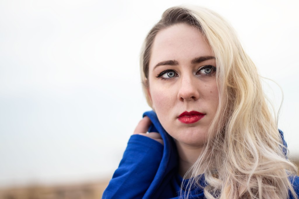 A blonde nonbinary woman with blue eyes, red lips, and curly hair looks over her shoulder into the distance.