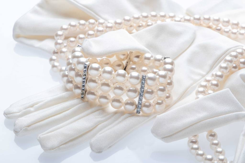 A three strand faux pearl bracelet with crystal and silver accents nestled on a pair of white opera gloves on white plexiglass. A double strand faux pearl necklace loops from the bracelet along the top of the image and down the left side to the fingers of the glove.