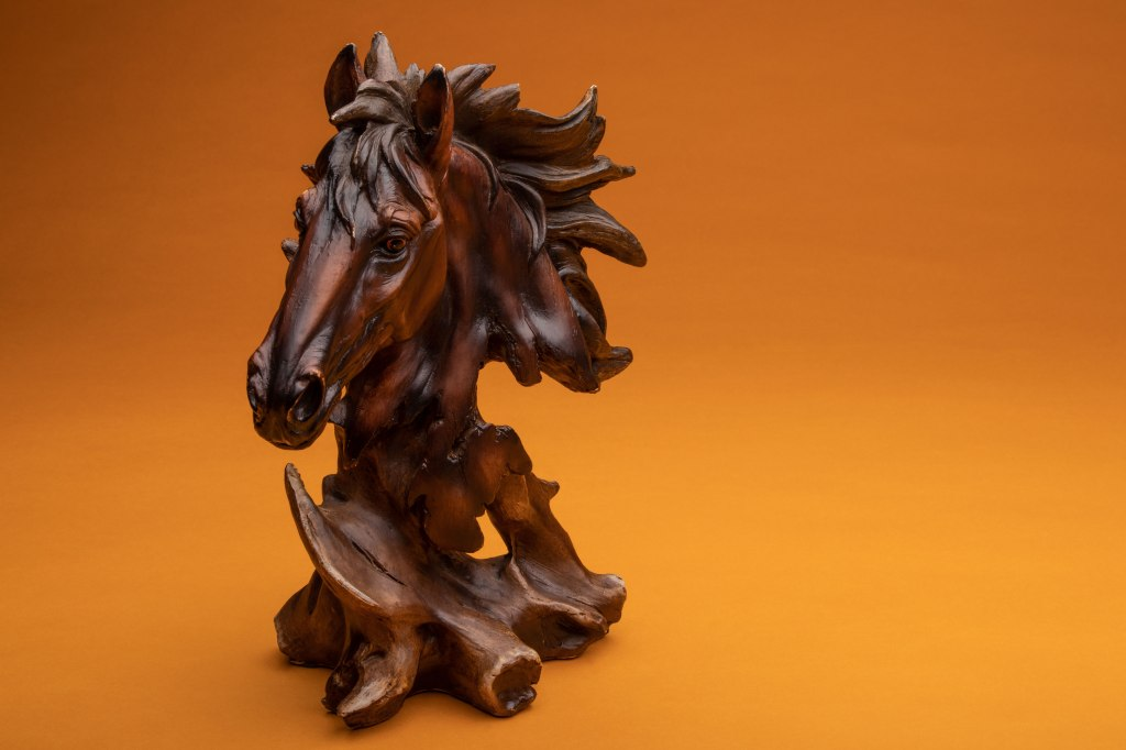 A statue of a horse's head carved out of wood on an orange background.