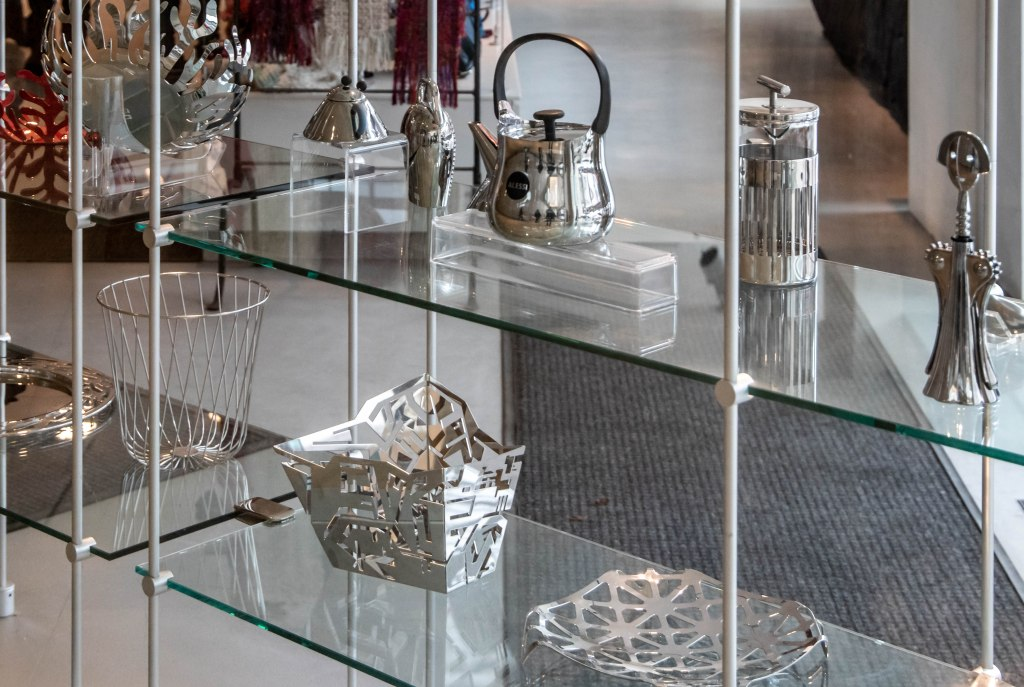 Silver tea kettles, grinders, shakers, baskets, plates, and other silver metal decor dazzle on the glass shelves of the window display to the gift shop inside the Overture Center in downtown Madison.