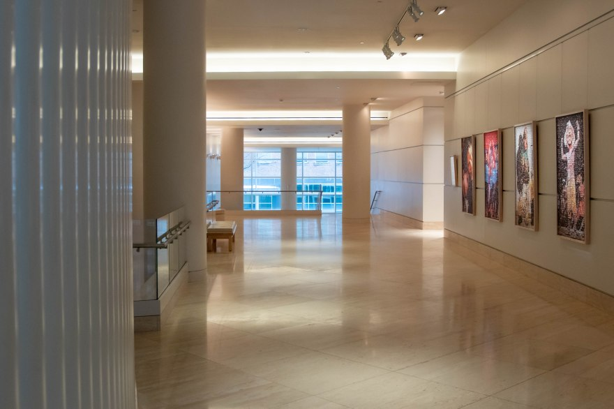 An expansive beige and white hall with colorful wall art of celebrity icons inside the Overture Center stretches empty to the far exit to the street in downtown Madison.