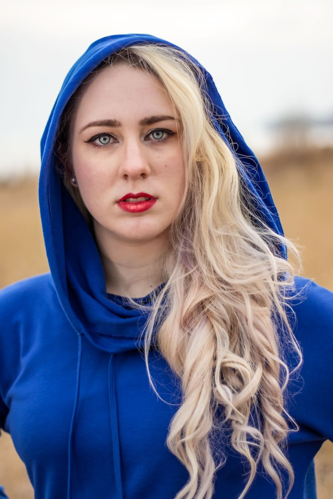 A nonbinary woman with long blonde curls, blue eyes and red lips stares at the viewer. She is wearing a rich navy blue hooded shirt.
