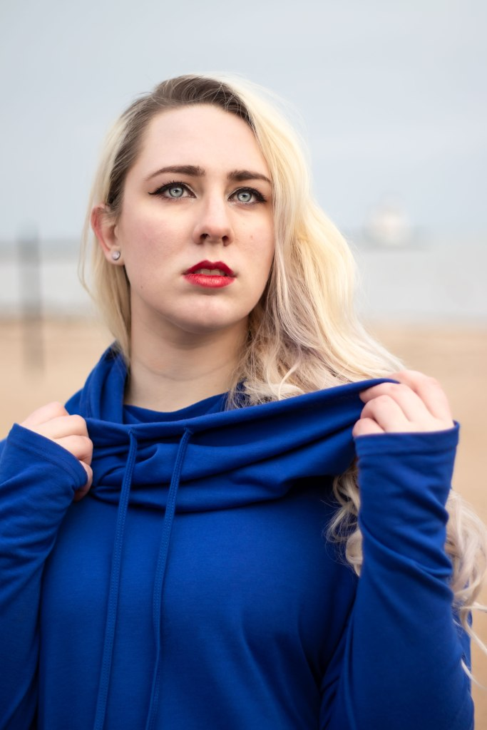 A nonbinary woman with long blond curls, blue eyes, and red lips stands in a rich navy blue hooded shirt, and the sandy beach and pier behind them fades into the hazy distance.