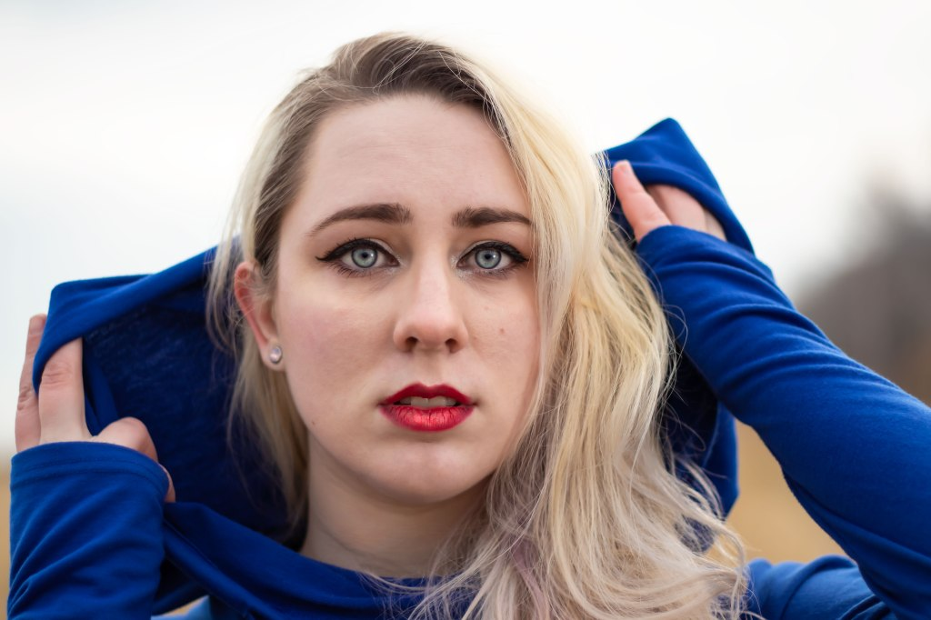 A blonde non binary woman with blue eyes and red lips throws back a rich navy blue hood.