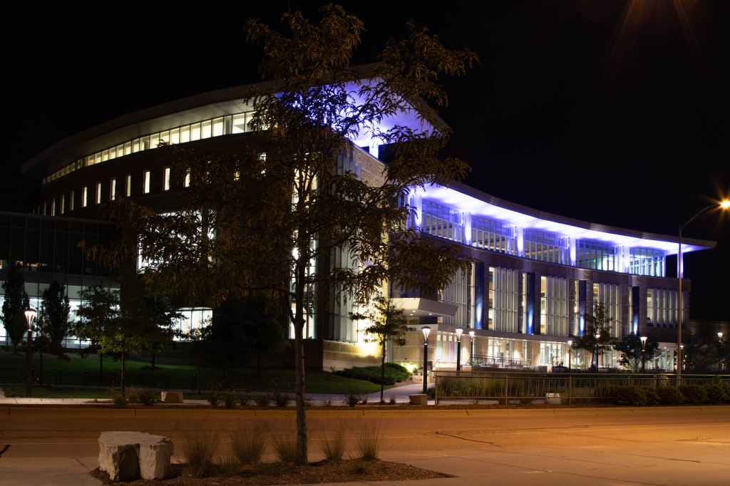 The  glass front of Truax Gateway building of Madison College lit up with blue at night. The building is seen from the left side across the street. A lamp post creates a brilliant start burst on the left.