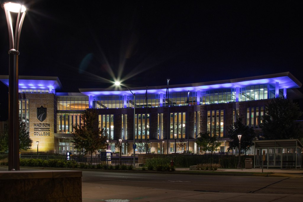 The  glass front of Truax Gateway building of Madison College lit up with blue at night. A lamp post stands bright at the left in the foreground, and one of the street lamps creates a striking star above the building.