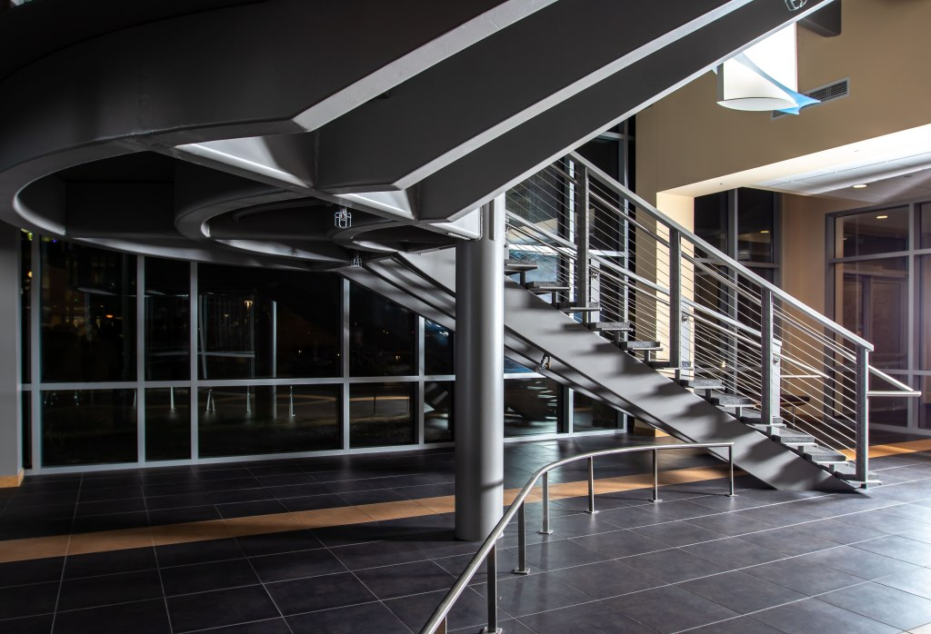First floor lobby of Truax Health Building at night. A meta railing curves away from the bottom left toward the grey staircase at the right that climbs diagonally across the image to the upper left, curves at the landing, and lifts again to exit the image at the upper right. A white cylindrical electric light fixture hangs in the center, wrapped in a decorative crescent of pale blue glass.