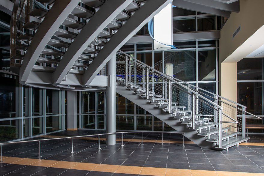 First floor lobby of Truax Health Building at night. A metal railing curves away from the bottom left toward the grey staircase at the right that climbs diagonally across the image to the upper left, curves at the landing, and lifts again to exit the image at the upper right. A white cylindrical electric light fixture hangs in the center, wrapped in a decorative crescent of pale blue glass.
