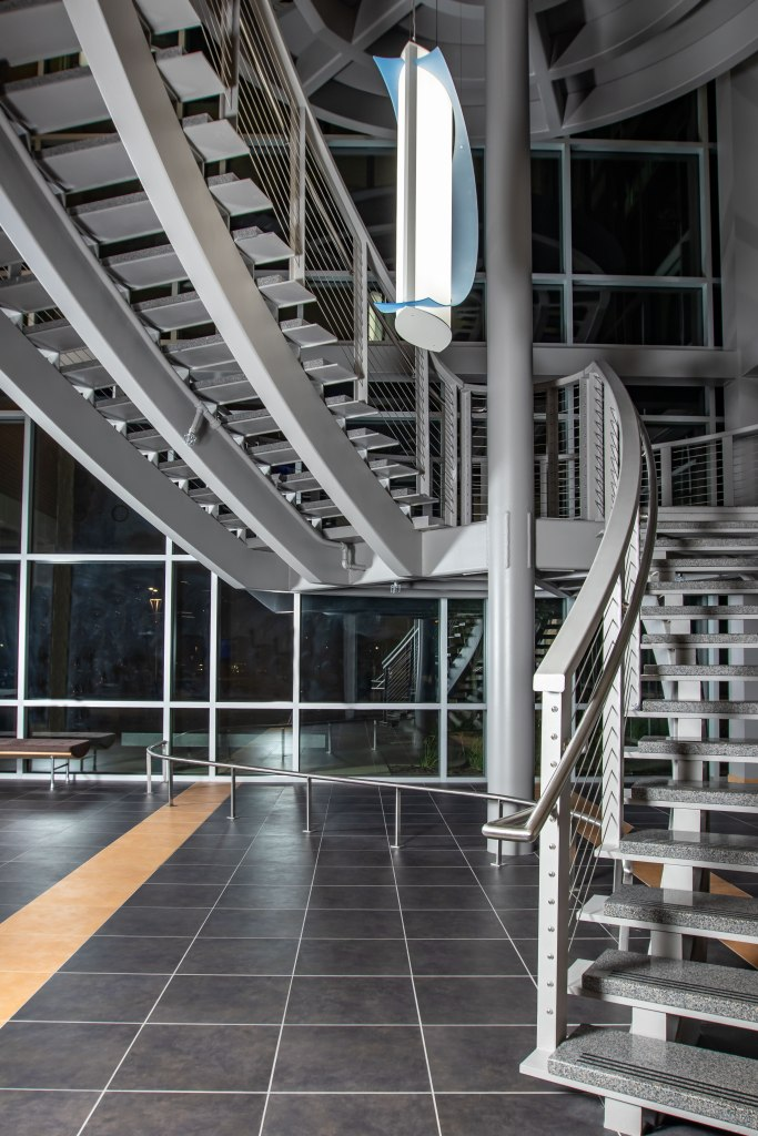 First floor lobby of Truax Health Building at night. A metal railing crosses from the bottom left toward the grey staircase at the right. the staircase opens toward the viewer, inviting them up to the half landing above. The stair climbs diagonally across the image to the upper left, to exit the image above. A white cylindrical electric light fixture hangs in the center, wrapped in a decorative crescent of pale blue glass.