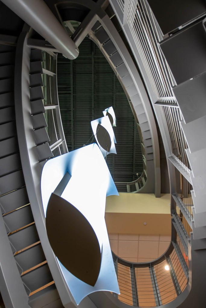 Abstract interior architecture image, looking up through the center of a grey oval shaped spiral staircase from first floor through the second floor to the ceiling on the third floor. The pale blue white crescent shaped lamps with eye shaped bases create a repeating pattern upward from the bottom left corner an diminish towards the center of the image.