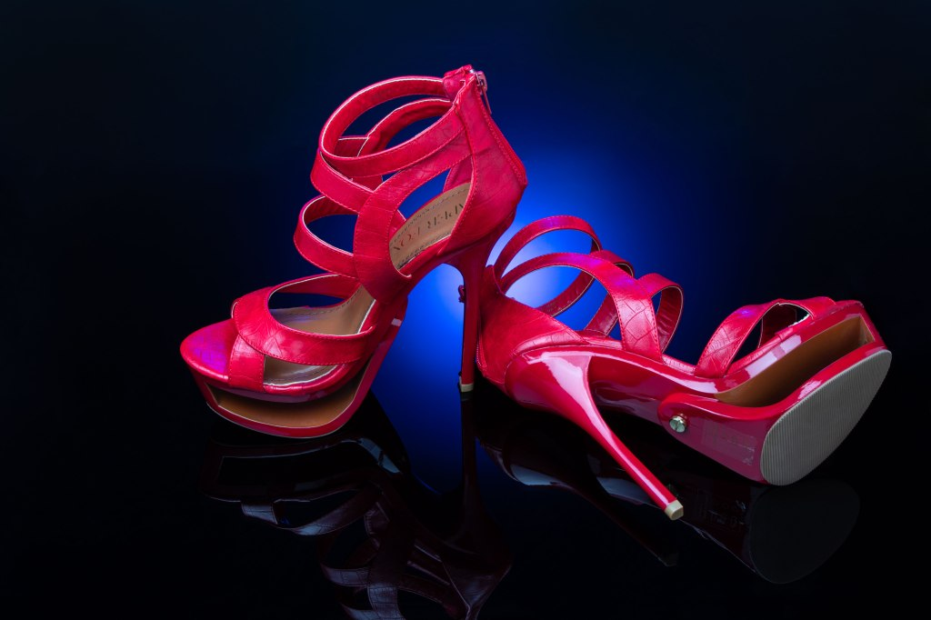 A sexy pair of glossy, strappy ruby red open-toe stiletto high heels gleam on a rich blue glow background that turns to black velvet at the edges. The reflection is seen in the plexiglass surface. The left heel stands upright and the right heel lays at an angle toward the viewer showing the detail of the gold hardware of the sole as well as the open cut of the hollow platform.