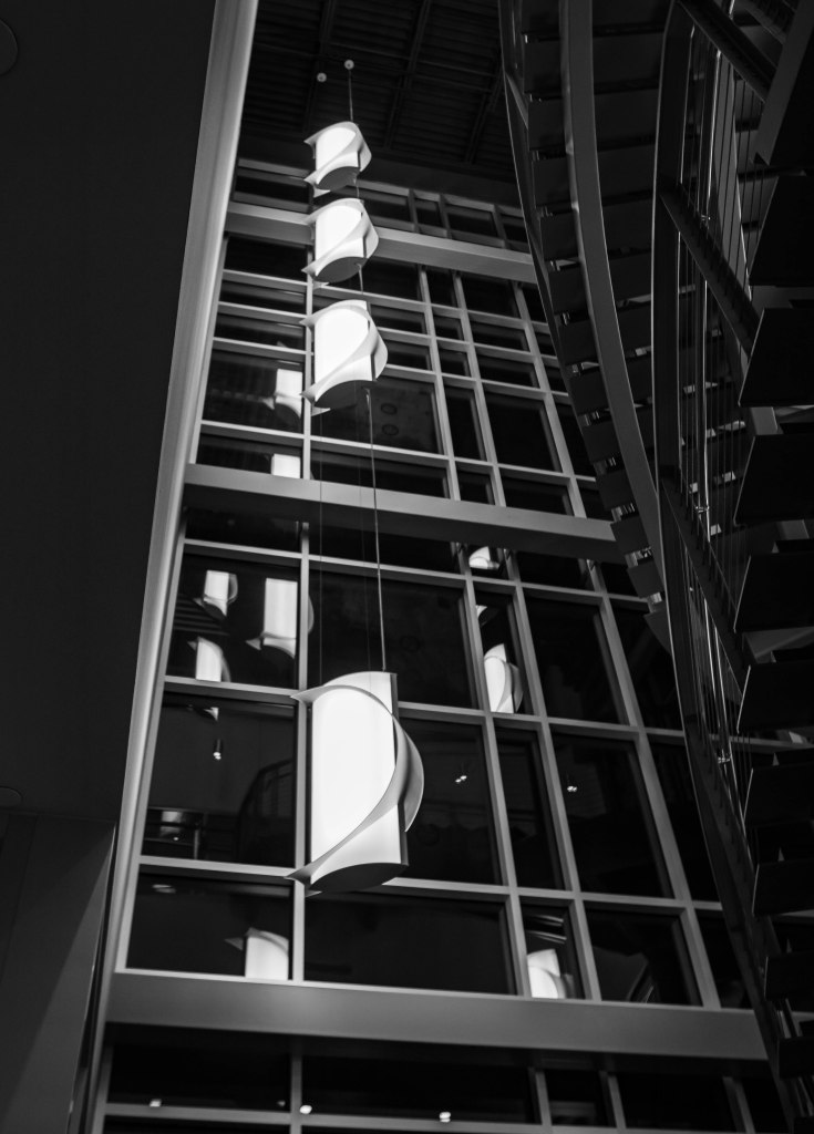 A greyscale image featuring the stunning four cylindrical hanging light fixtures wrapped in crescent moons descending from the Truax Health Building at Madison College, reflected in the strong silver lines of the three-story windows.