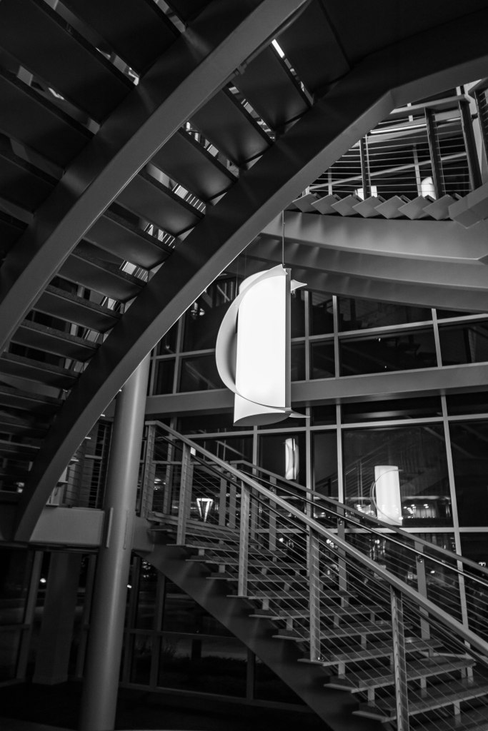 A greyscale image of a wrap around staircase in a modern design leading up three floors. Center is a white cylindrical decorative suspended light. Beyond the light and stairs, the entire view is reflected in three story glass windows.