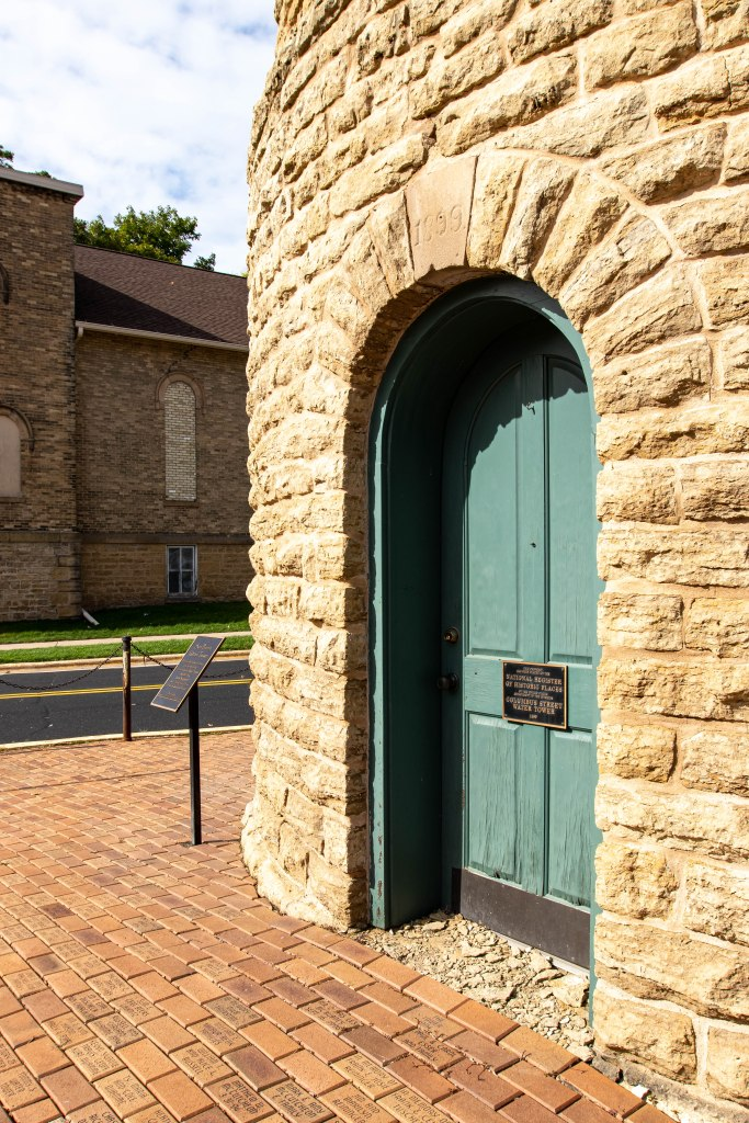The rounded green wooden door set in the curved stone archway of the Colombus Street Water Tower in Sun Prairie, WI. The plaque on the door displays it is a historic landmark.