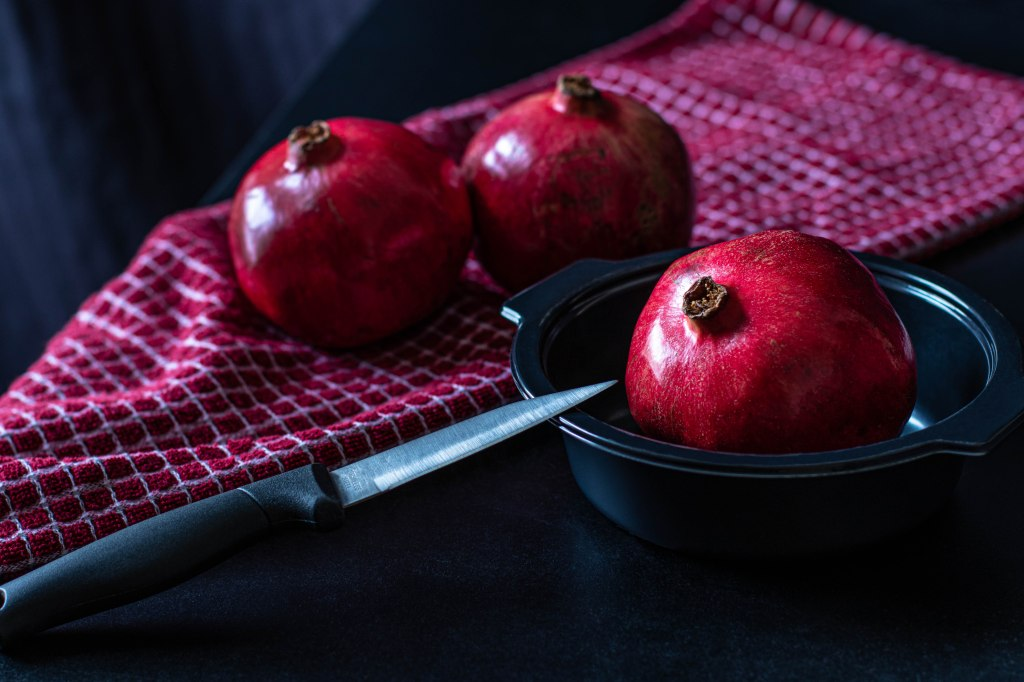 A crimson pomegranate sits in a black bowl on a black table. A knife lies precariously on the edge of the bowl, pointing toward the fruit. Twin pomegranates on a red and white checked cloth frame the background.