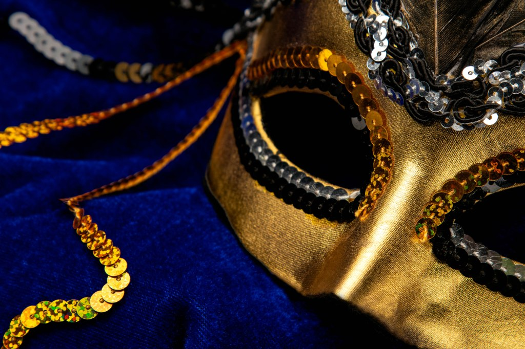 A mysterious shiny, reflective gold lamè  half mask fills the right half of the image, draped at a upward tilting diagonal toward the center on a blanket of rich royal blue velvet. The eyes are edged with gold sequins across the top and silver and black sequins underneath. Silver and black sequins weave into a crown across the top of the mask below a spill of black feathers. Two gold strandsand one black strand of decorative sequins trail in corkscrew tendrils from the ear of the mask in the center and fan off the image, exiting at each corner and the center left.