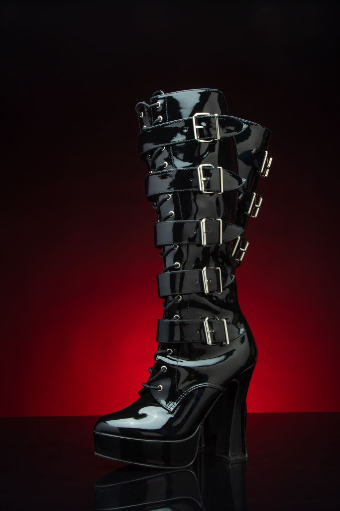 A sexy pair of black patent leather fetish BDSM alternative knee-high lace-up platform boots with five straps and silver industrial buckles from ankle to knee on black plexiglass with a crimson red glow in the background.