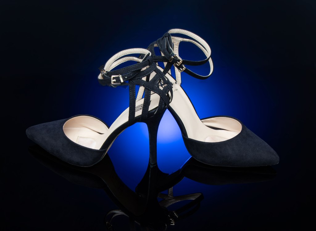 A sexy pair of black velvet stilettos stand tall on a richly blue glowing background that fades to black at the edges. The toes and pointed and the black straps tease and peek at the heel before winding around the ankle. The shoes point in opposite directions with the illusion that there is only one wine stem glass slender heel that then flows into infinity through the reflection in the black plexiglass.