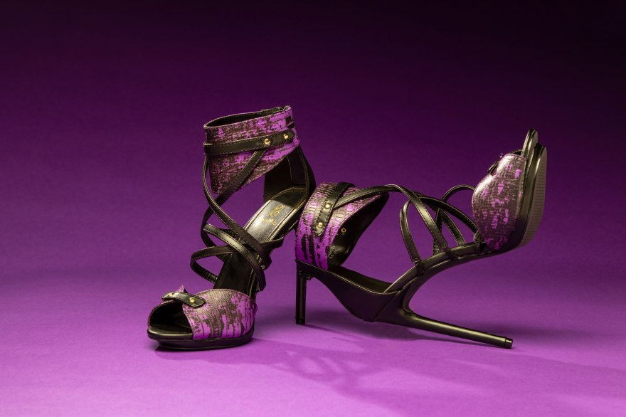 A sexy, wild pair of edgy purple stiletto high heels with criss cross black straps against a rich purple gradient background. The high heel on the left stands upright, and the one on the left balances against it with the toe pointed to the heavens.