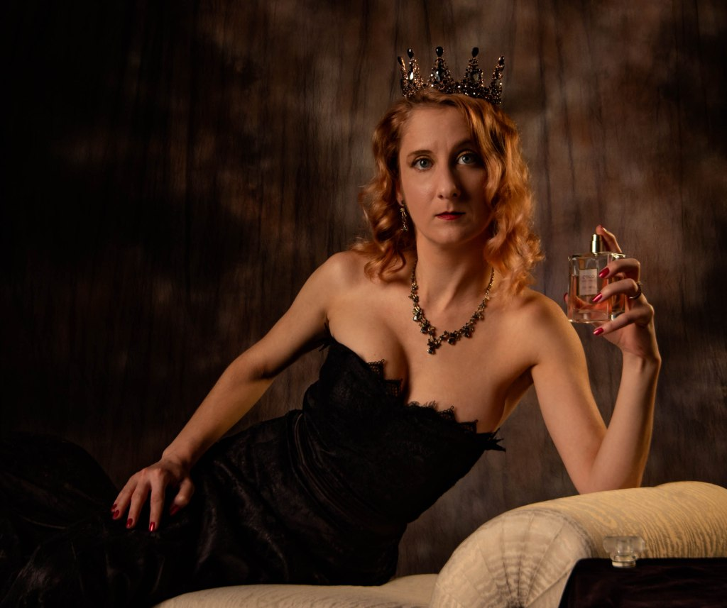 A woman with shoulder length curly red hair and blue eyes reclines on a white couch with one elbow against a rich brown background. She wears an elegant bare shoulder black lace gown and a black gemstone tiara. She is ruby red lips and nails. One hand rests on her hip, the other holds a bottle of Chanel perfume.