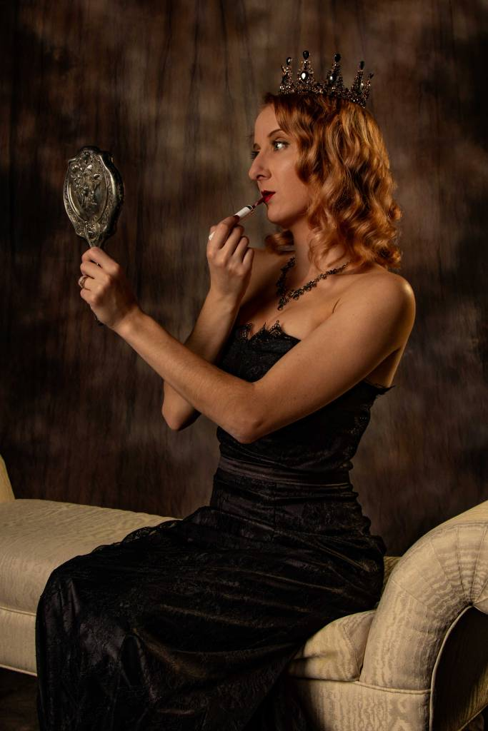 A redhead with shoulder length curls and big blue eyes paints her lips ruby red while looking into an antique silver handheld mirror. She wears a black gemstone tiara and necklace and a bare shoulder black lace dress. She is seated on a low chaise longue couch against a rich velvety brown background.